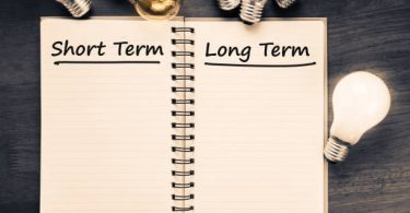 Short term and Long term on opened notebook with glowing light bulb